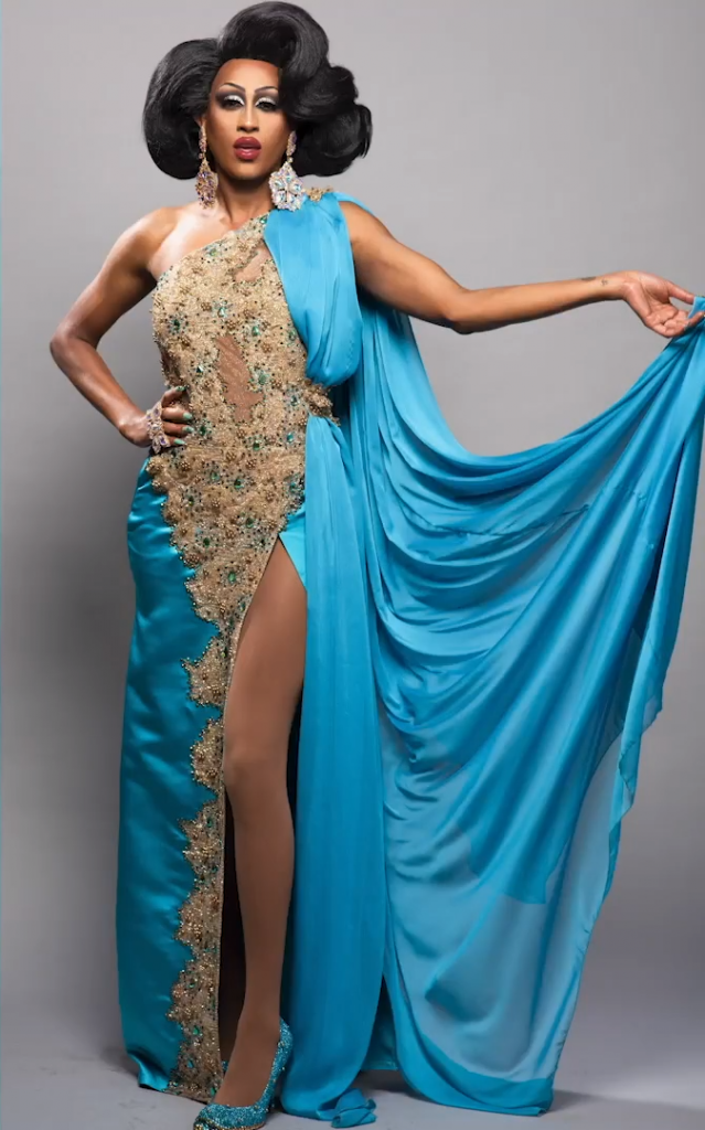 Priyanka, a drag queen on Canada's Drag Race. she describes her heritage as Indo-Caribbean. in this photo, Priyanka is wearing a blue and gold sari with one leg exposed, her black hair is styled big and parted on the side into two perfect asymmetrical swooshes. i cannot describe fashion, unfortunately. but she's gorgeous!!