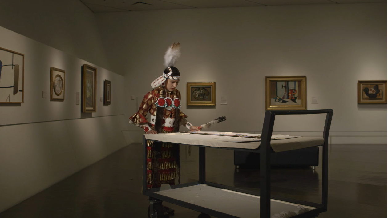 a video by Jeffrey Gibson called 'one becomes the other'. the film is set in the Denver Art Museum. Indigenous people in ceremonial dress populate the film, examining artifacts on display throughout the museum and in the archives.