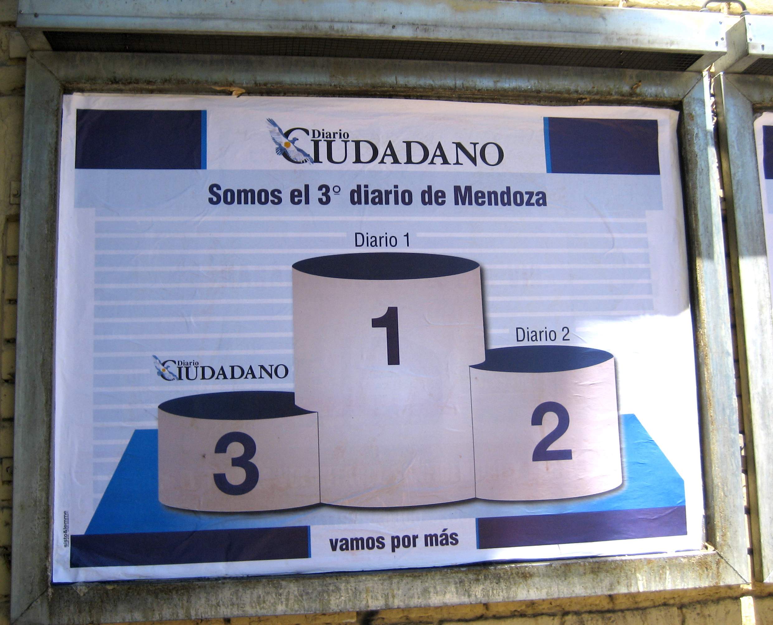 "a photo from 2007 of a poster in Mendoza, Argentina that i thought was hilarious. a bus ad for Diario Ciudadano features a cartoon of a first-, second-, and third-place podium. Diario Ciudadano is third place. two unnamed newspapers, ""Diario 1"" and ""Diario 2"" are ahead of them. large letters at the top of the poster says, ""Somos el tercero diario de Mendoza"", or ""we are the third-place newspaper in Mendoza."" in small letters at the bottom of the poster is what i assume is their tagline. ""vamos por más,"" or ""let's go for more."""