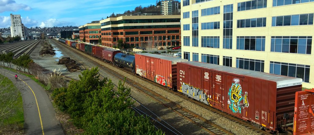 a photograph of a semi-urban city. multi-colored train cars stretch from the upper-left to lower-right of the picture. the train is mostly boxcars, though there is a black tanker in the middle. the tracks run next to  a few buildings on one side. they're all about five stories tall. on the other side of the track is a bike/run path that curves slightly to the left. a single cyclist is on this side of the tracks.