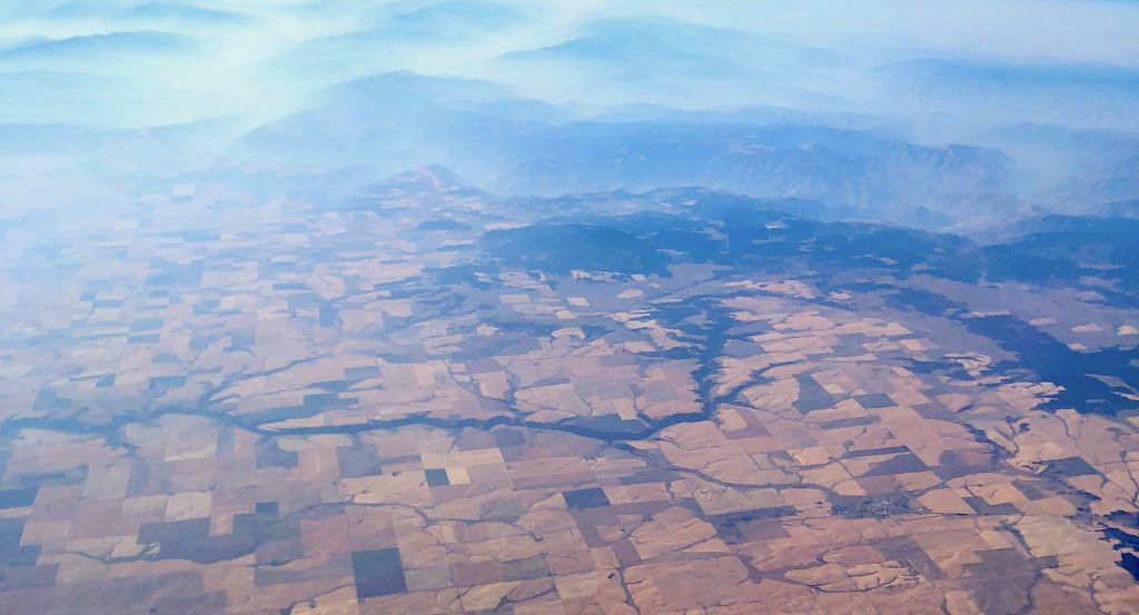 a photo of the countryside as seen from the window of a plane. the upper third of the picture contains slowly undulating hills in misty blues and greens. the rest of the frame is a birds-eye patchwork of farms and natural features.