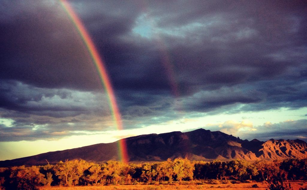 a photo of the mountains outside Albuquerque, New Mexico. above the mountains in the shadows of dusk sit dark clouds with flecks of light. in front of the mountains are desert trees and grass cast in a ghostly yellow-brown. somewhere between the viewer and the scrub trees, a rainbow floats in the ether. near the center of the image is a second rainbow, barely visible, but perhaps the thing that made this scene so special.