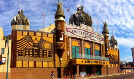 the world's only corn palace in Mitchell, SD. the building is ostentatious and tacky. red brick and thatched corn husk serve as most of the building's face. flanking the entrance are two friezes made of cobs of light and dark corn. atop the building are five metallic minarets. the sky is blue with light clouds stretching end to end.