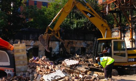 a piece of heavy machinery clears wreckage from a demolition site