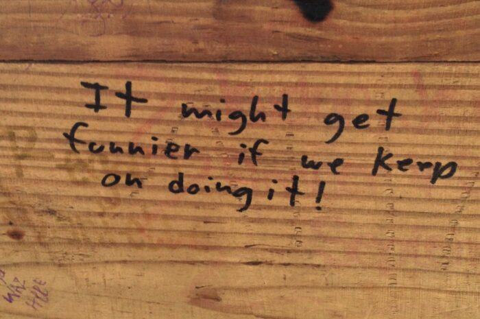 handwritten graffiti in Sharpie on a piece of wood