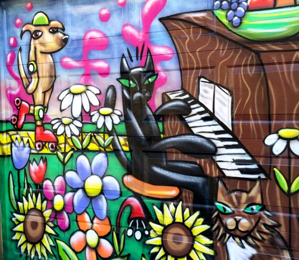 a spray paint mural of a few animals doing fun stuff in a field of flowers