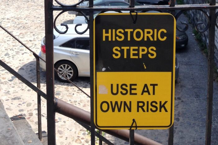 """a yellow and black sign that reads, """"historic steps"""" and """"use at your own risk"""""""